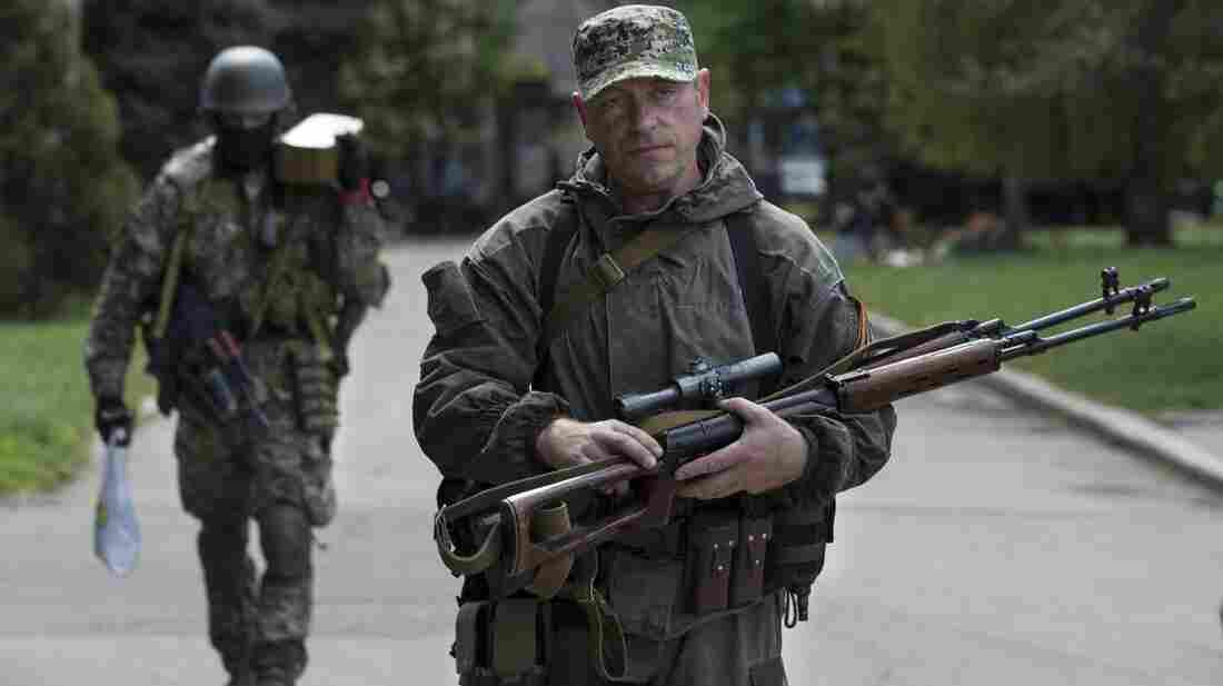 Pro-Russian gunmen carry their weapons in the center of Slovyansk, Ukraine, Tuesday. Gun battles were fought around