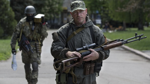 Pro-Russian gunmen carry their weapons in the center of Slovyansk, Ukraine, Tuesday. Gun battles were fought around the city Monday in what has proven the most ambitious government effort to regain control of areas taken by separatists. (AP)