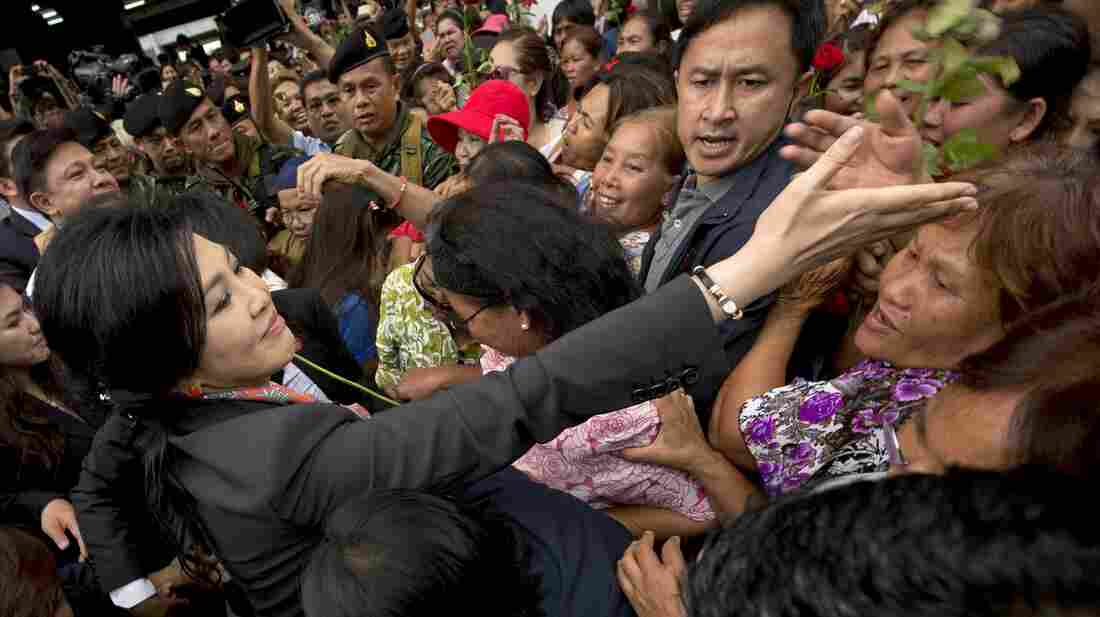 Ousted Thai Prime Minister Yingluck Shinawatra received roses from supporters in a Bangkok suburb on Wednesday.