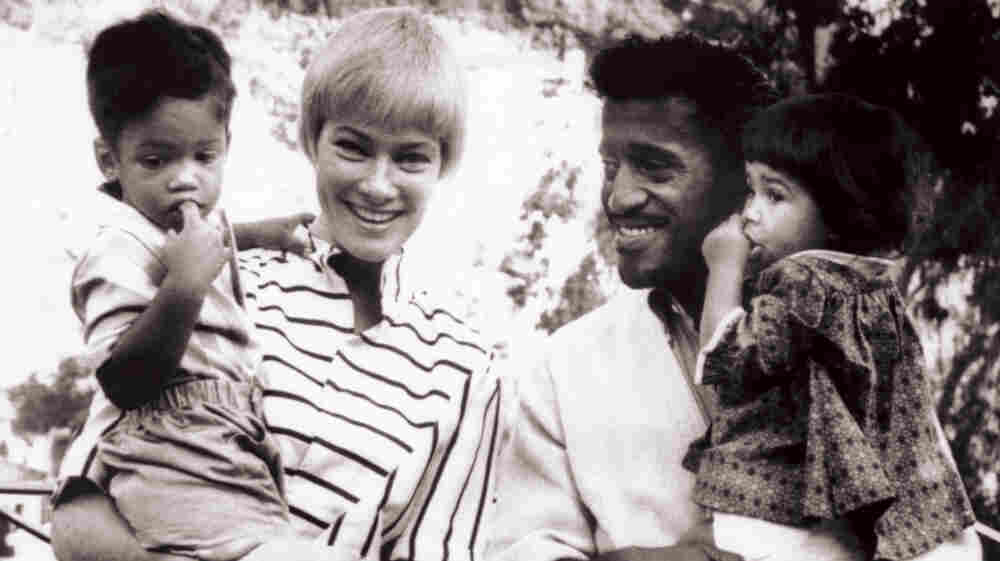 Sammy Davis, Jr. holds daughter Tracey in a family picture taken in 1962.