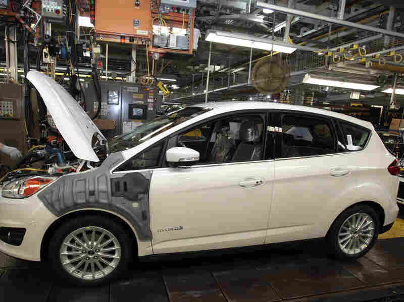 A Ford Motor assembly employee works on a 2013 Ford C-MAX Hybrid vehicle at the Michigan Assembly Plant in Wayne, Mich., on Nov. 8, 2012.