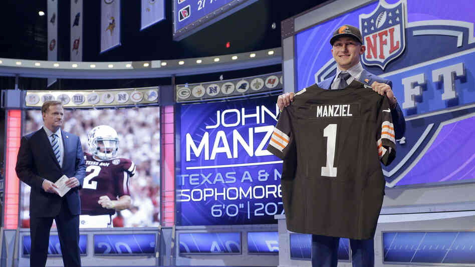 Texas A&M quarterback Johnny Manziel poses for photos after being selected by the Cleveland Browns as the 22nd pick in the first round of the 2014 NFL Draft, Thursday.