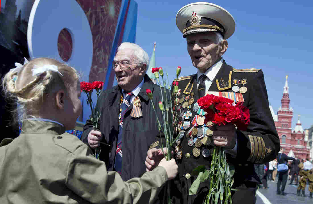 A girl gives flowers to World War II veteran Ivan Bobarykin after Friday's Victory Day parade in Red Square in Moscow. Thousands of Russian troops marched in the annual parade.