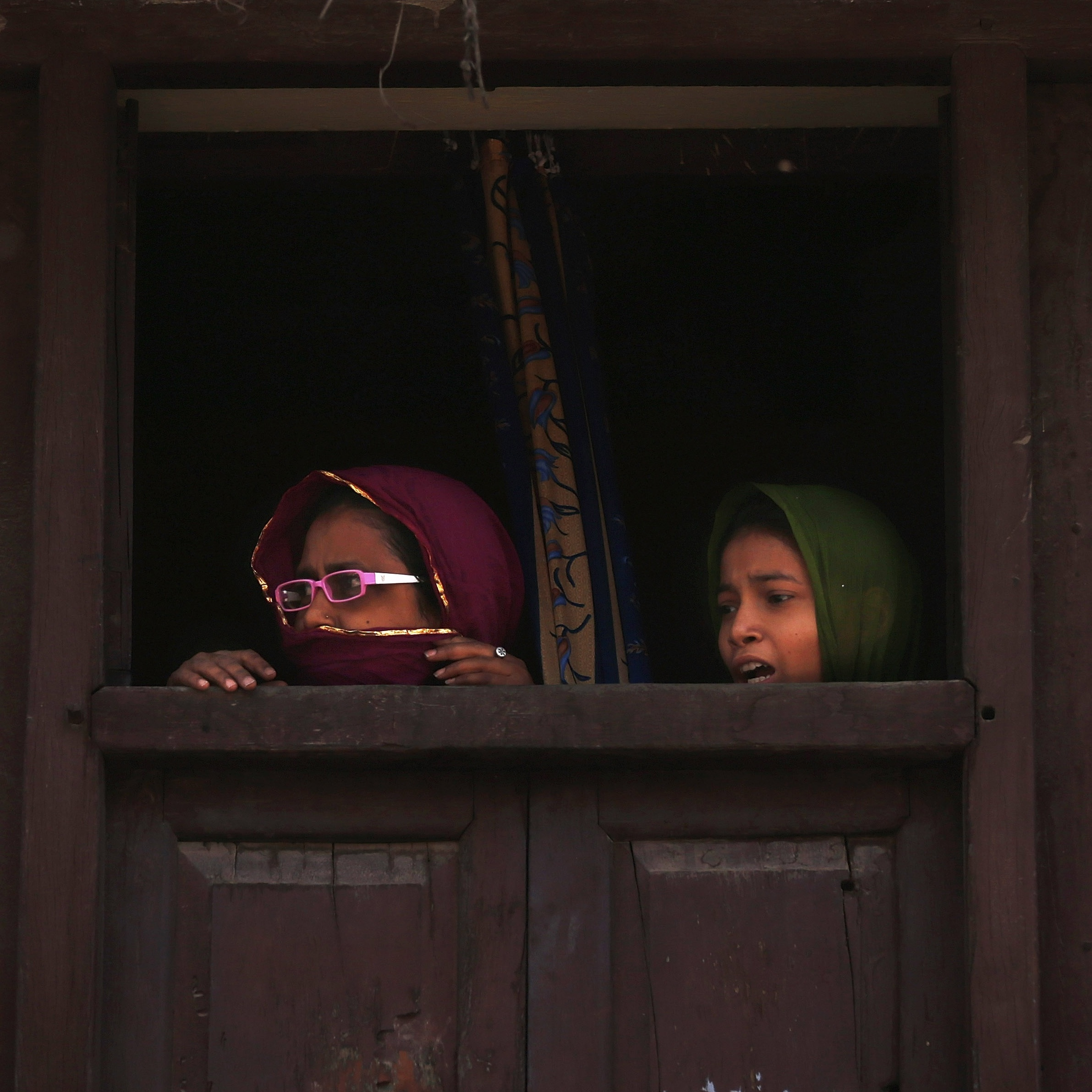 Muslim women watch Modi's rally move by in Varanasi. Most Muslims oppose Modi and fear that he would cut them out of the region's growing prosperity.