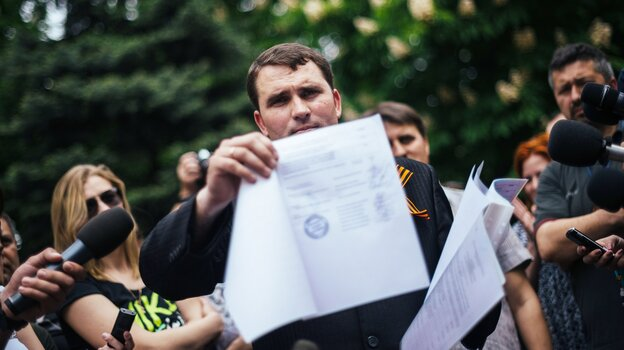 "In the eastern Ukrainian city of Lugansk, the ""chairman of the Central Election Commission"" Alexander Malykhin shows a document with the results of a referendum outside the regional state administration building Monday. He said voters had chosen to leave Ukraine."