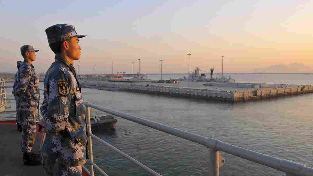 Chinese sailors stand guard on China's first aircraft carrier as it travels toward a military base in Hainan province. China has been waging a public crackdown on military corruption, perhaps the largest such campaign in more than six decades of communist rule.