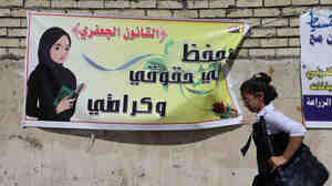 "An Iraqi schoolgirl passes a banner supporting a proposal that, among other things, would allow men to marry girls as young as 9. Opponents say it would mark a major setback for women and children. The Arabic on the banner reads: ""The Jaafari Personal Status Law saves my rights and my dignity.&quot"