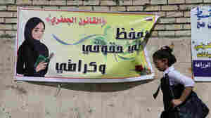 """An Iraqi schoolgirl passes a banner supporting a proposal that, among other things, would allow men to marry girls as young as 9. Opponents say it would mark a major setback for women and children. The Arabic on the banner reads: """"The Jaafari Personal Status Law saves my rights and my dignity."""""""