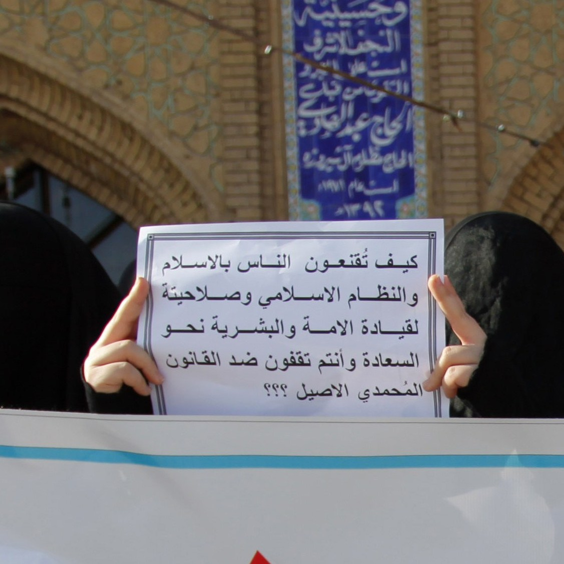 Iraqi women in Najaf hold up a placard in support of the Jaafari law in March. The law is based on the principles of the Jaafari school of Shiite religious jurisprudence. It prohibits Muslim men from marrying non-Muslims and lowers the marriage age to 9 for girls and 15 for boys.