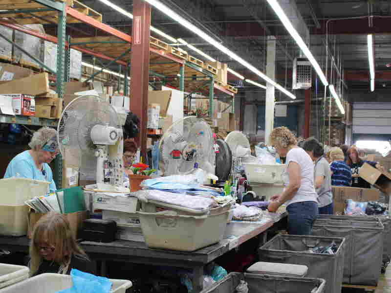 AmeriMark employees sort through return orders on the catalog company's processing floor.