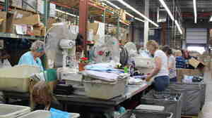 AmeriMark employees sort through return orders on the catalog company's processing floor.