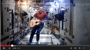 """Screen grab from astronaut Chris Hadfield's rendition of David Bowie's """"Space Oddity"""" — performed on the International Space Station."""