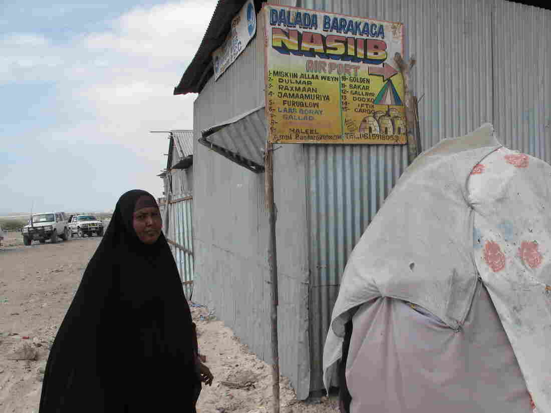 Adad Hassan Jimali stands next to a sign for her private camp for displaced persons. The camp, which is in Mogadishu, Somalia, is called Nasiib Camp.