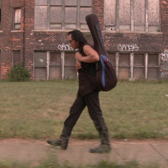 Rodriguez carries his guitar through Detroit, his hometown.