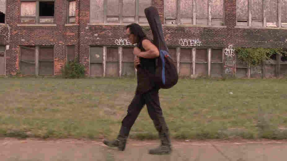 Rodriguez carries his guitar through Detroit, his hometown.