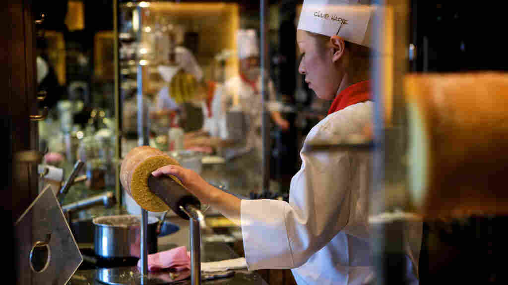 A chef prepares the baumkuchen, a German layer cake made on a stick that when cut, resembles a tree with concentric rings.