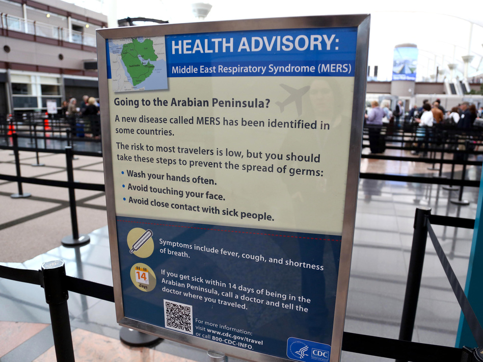 A sign at the Denver International Airport warns travelers about the dangers of the Middle East respiratory syndrome virus.