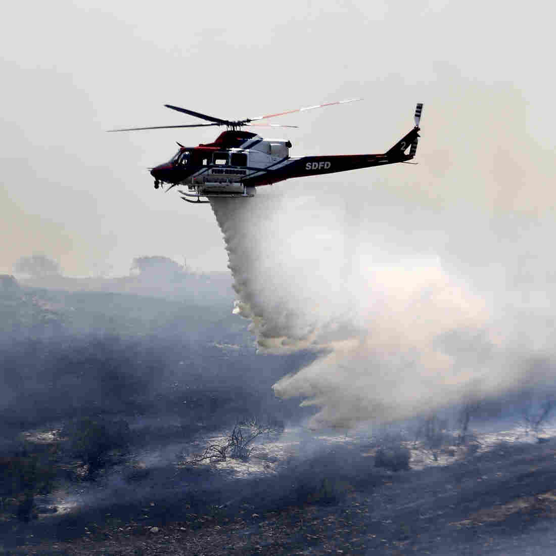 A helicopter attacks a wildfire burning in the north county of San Diego on Tuesday.