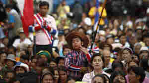 An anti-government protester waves the Thai flag during a rally in Bangkok, on Wednesday.