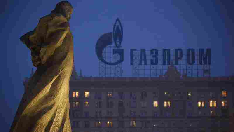 A monument to Ukrainian writer Taras Shevchenko is silhouetted against a sign advertising Russia's natural gas giant Gazprom in Moscow. Gazprom has dramatically increased the price it charges Ukraine in recent months.