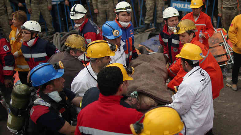 Rescue workers carry a man from the coal mine in Soma, western Turkey, site of a disaster that has killed 245 people.