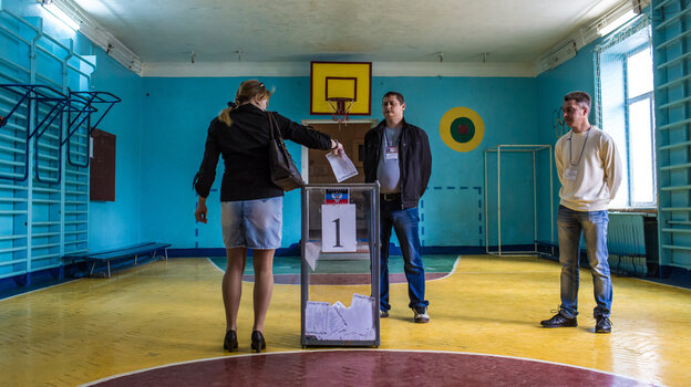 A woman casts her ballot at a polling station on
