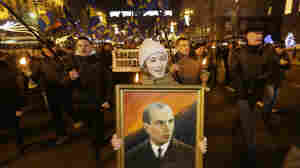 A Ukrainian nationalist carries a portrait of Stepan Bandera, founder of a Ukrainian rebel army that fought the Soviet Union in the 1930s and '40s. The rally was held on Jan. 1, 2013. While many Ukrainians see Bandera as a hero, many Russians view him as an ally of Hitler and a mass murderer.