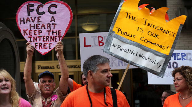 """Demonstrators protest outside the Federal Communications Commission Thursday. The agency voted to open new proposed rules for public comment, including a discussion of whether """"paid prioritization"""" should be banned."""