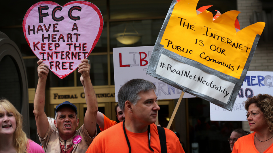 "Demonstrators protest outside the Federal Communications Commission Thursday. The agency voted to open new proposed rules for public comment, including a discussion of whether ""paid prioritization"" should be banned."