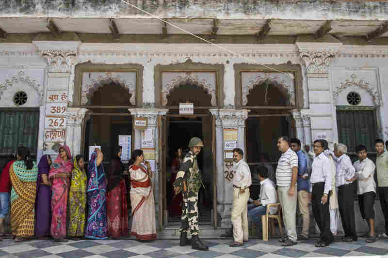 A Border Security Force officer stands guard as Indian citizens wait in line to vote at a polling station on May 12.
