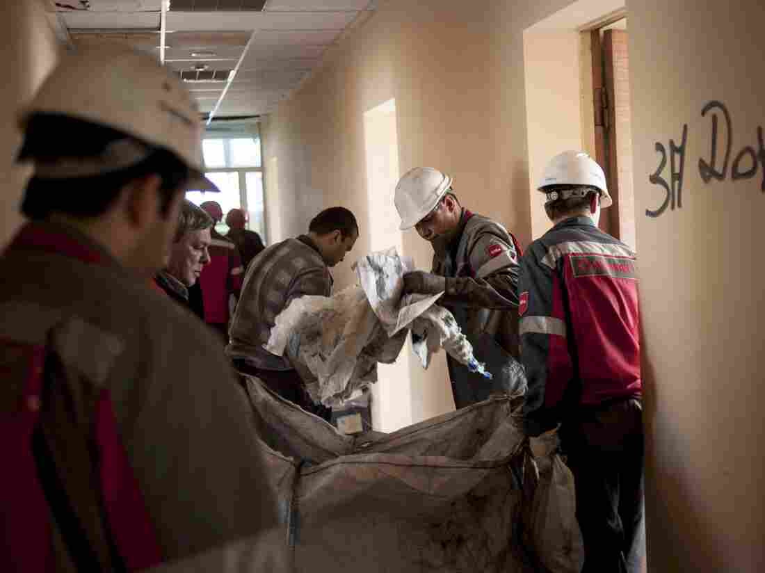 Workers of the Ukrainian company Metinvest clear away debris in a government building in the eastern Ukrainian city of Mariupol on Friday. Local patrols by steelworkers have forced pro-Russia separatists to retreat from the government buildings they occupied.