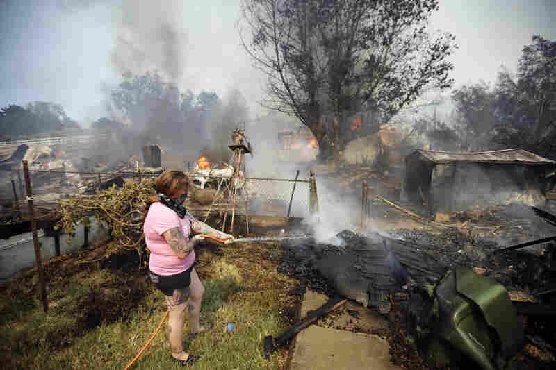 A woman douses debris around her home as her neighbor's home burns Thursday in Escondido.