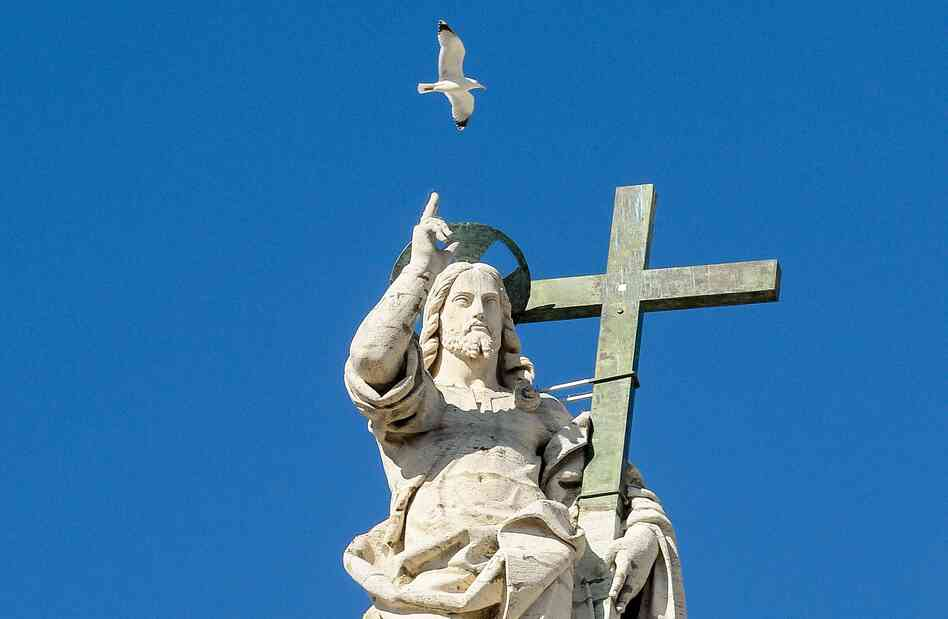 "A seagull flies over a statue of Jesus on the top of St. Peter""s Basilica in Rome."