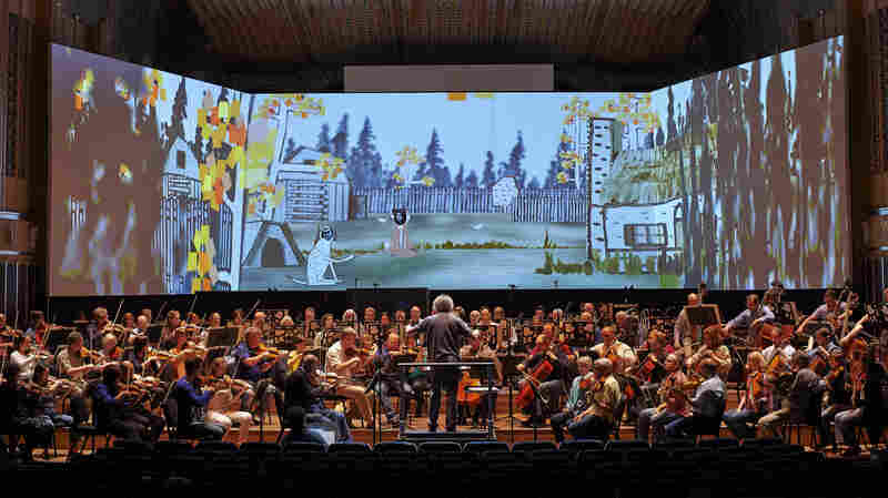 In a scene from the Cleveland Orchestra's The Cunning Little Vixen, two actors (Julie Boulianne as Dog and Martina Jankova as Vixen) appear from behind a computer-animated backdrop.