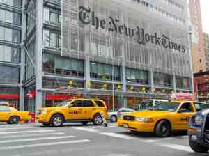 Taxis speed past the headquarters of the New York Times.