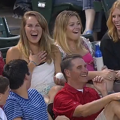 A boy hands a girl a foul ball and she smiles broadly.