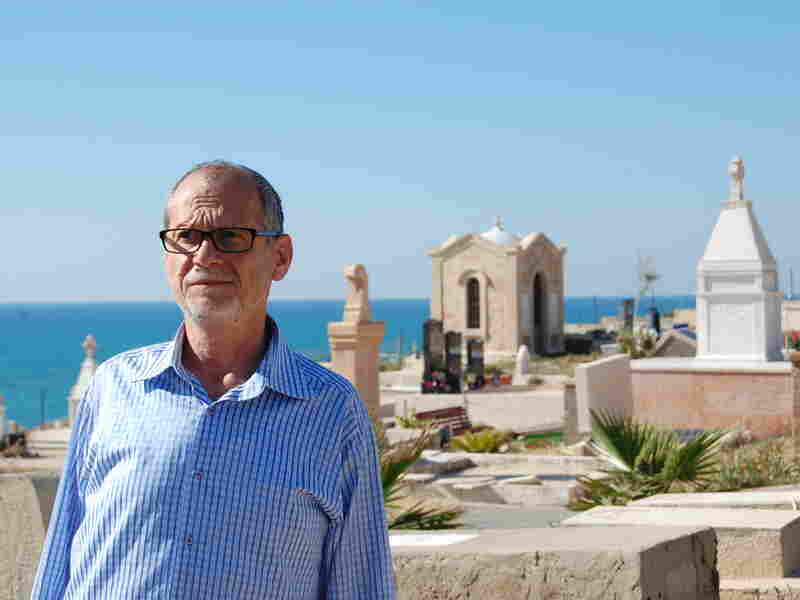 """Peter Habash, an Arab Christian, stands at a Christian graveyard in Jaffa. """"We have no connection"""" with migrant or Russian Christians, he says."""