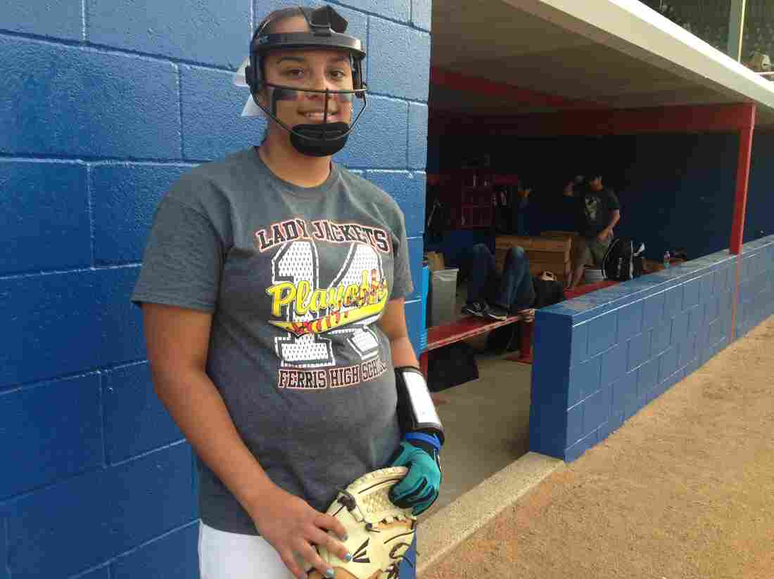 Ferris High School softball player Kylee Fowler stands beside the dugout, face mask on and ready.