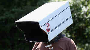 An anti-surveillance protester stands outside the Bilderberg conference last year in Watford, England. This year the conference may be in Denmark.