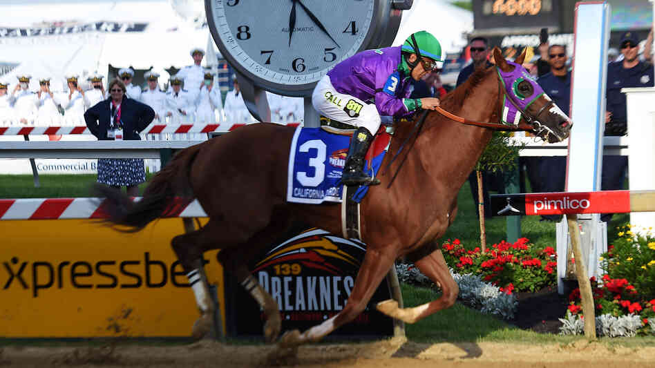 California Chrome, ridden by Victor Espinoza, crosses the finish line to win the Preakness Stakes on May 17 in Baltimore.