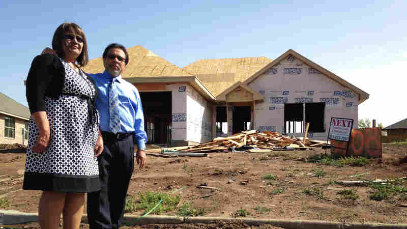 Gloria and Francisco Sanchez stand in front of their new ranch house, still under construction a year after a tornado destroyed their last home in Moore, Okla.