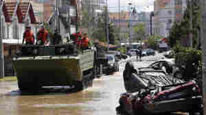 A military amphibious vehicle heads down a flooded street in Obrenovac, Serbia. Residents were preparing for a river surge Monday that threatened to inundate Serbia's main power plant.