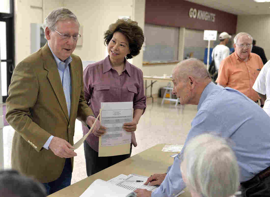 Kentucky Republican Senator Mitch McConnell, left, and his wife Elaine Chao, center, talk with poll workers at their precinct Tuesday, May 20, 2014, at Bellarmine University in Louisville, Ky.