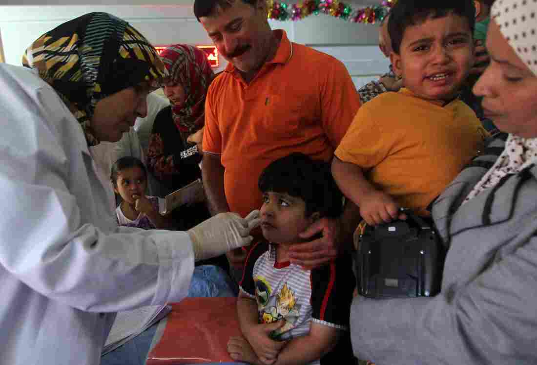 A doctor gives a polio vaccine to a child at a health clinic in Baghdad last week. The CIA says it banned the use of vaccine programs as cover for spying last year — a practice health officials said had wide repercussions.