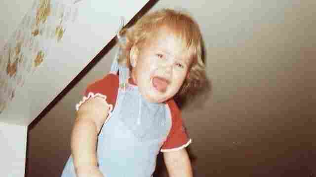 """Debra Jenson, 2, hanging from a hook in her grandmother's kitchen. """"Over the next 35 years, I watched each of my cousins, then my own children and my cousins' children be dangled from that hook. Between the photo and watching it happen to others, this is a powerful 'fake memory' for me."""""""