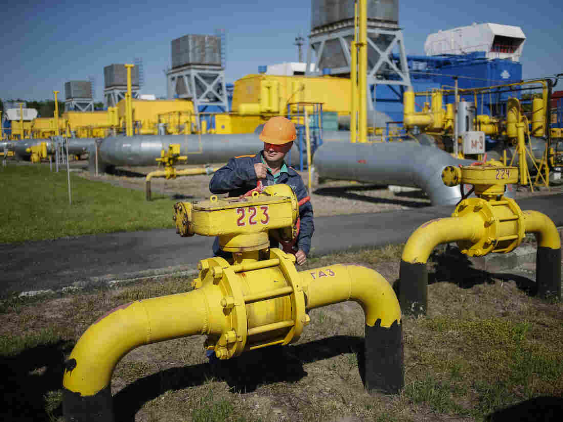 A worker turns a valve at an underground gas storage facility near Striy on Wednesday. Russia has said state-controlled exporter Gazprom will supply China with natural gas via a Siberian pipeline beginning in 2018.