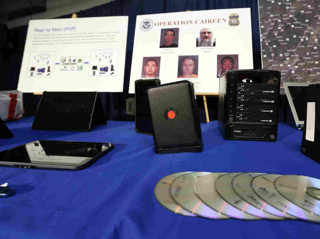 Hard drives, computers and other electronic devices seized as part of Operation Caireen along with photos of some of the 71 individuals arrested in connection with the investigation.