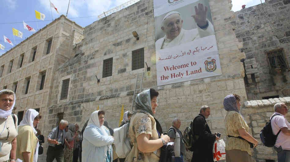 Tourists walk past a poster of Pope Francis hanging on the Church
