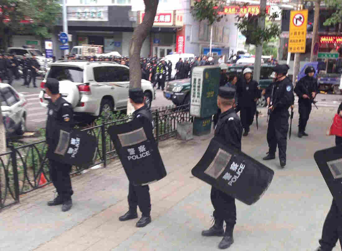 A photo released by China's Xinhua News Agency shows police standing guard near a blast site in downtown Urumqi. Officials say 31 people died in the attack.