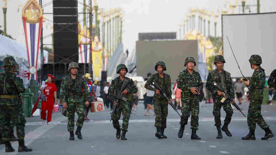 Thai soldiers move in on a pro-government demonstration on the outskirts of Bangkok on Thursday. Thailand's army chief Gen. Prayuth Chan-Ocha has announced a military takeover of the government, saying the coup was necessary to restore stability after six months of political turmoil.